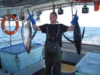 Deckhand proudly holding two large fresh tuna.